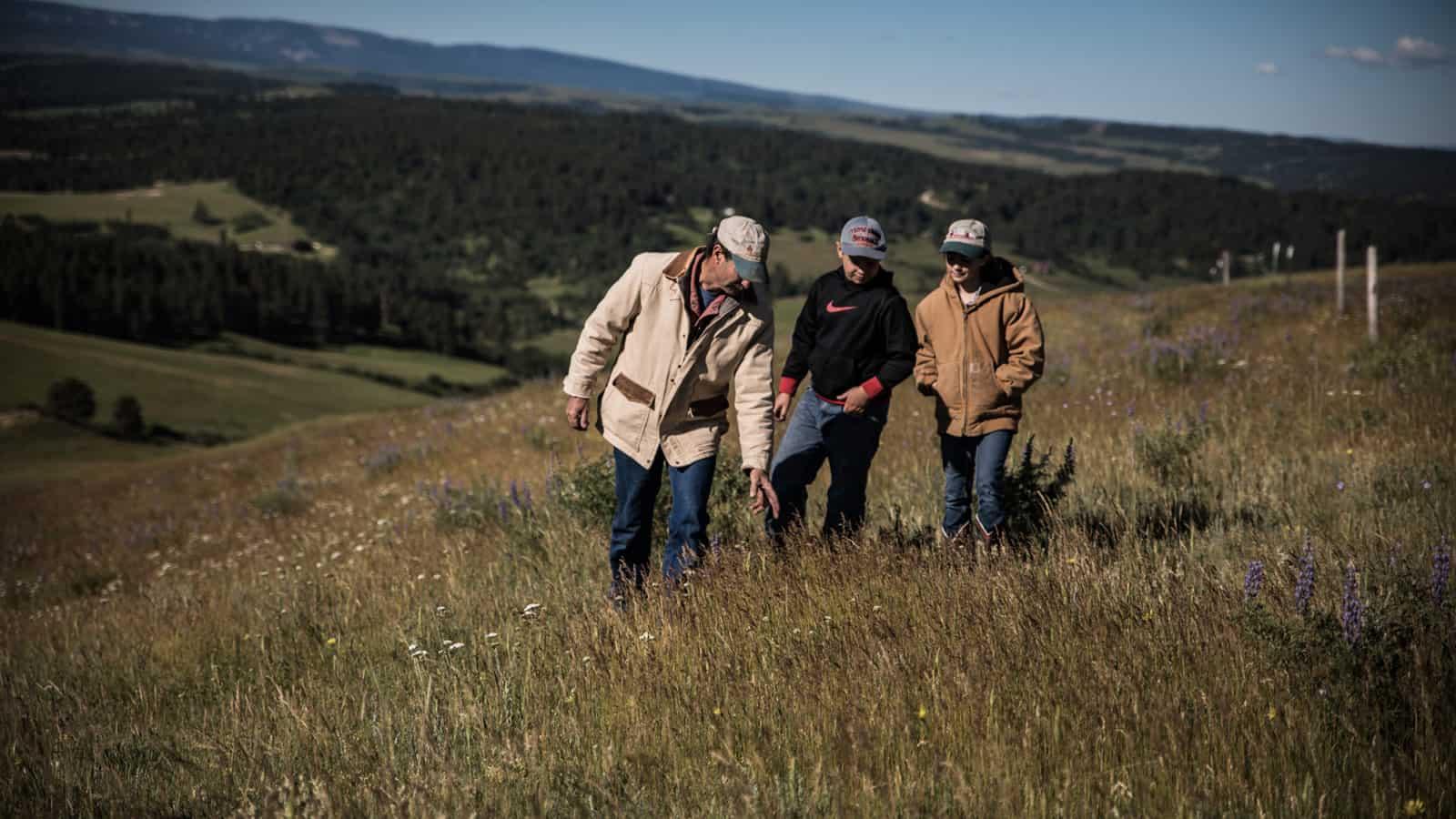 Men standing in pasture
