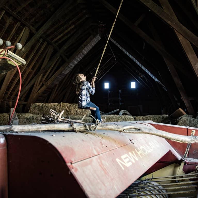 Girl on rope swing inside old barn